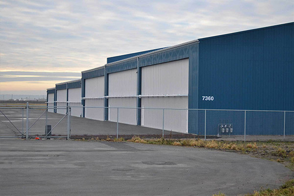 commercial warehouse facility hangar with fencing