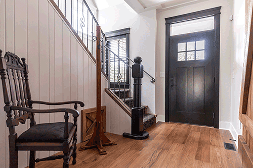 home interior front door and stairs with dark wooden antique chair