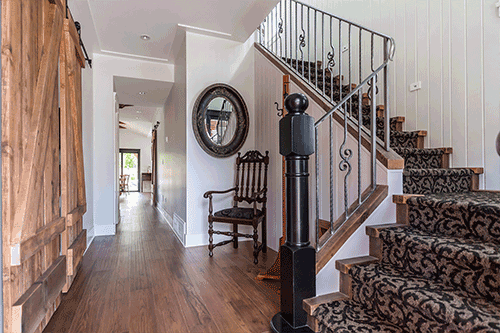 home interior with floral design carpet stairway with rustic wooden doors and hardwood floors